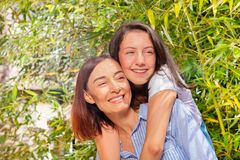 Happy teenage girl giving her mother back hug. Portrait of happy teenage girl giving her mother back hug outdoors at sunny day royalty free stock photography