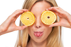 Portrait of happy teenage girl holding lemon in front of eyes Stock Photo