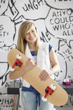 Portrait of happy teenage girl holding skateboard at home Royalty Free Stock Image