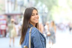 Happy teenage girl looks at camera in the street. Portrait of a happy teenage girl looks at camera standing in the street royalty free stock image