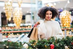 A portrait of teenage girl with paper bags in shopping center at Christmas. A portrait of happy teenage girl with paper bags in shopping center at Christmas royalty free stock images