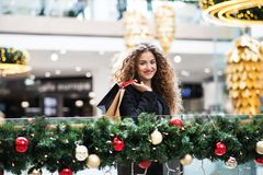 A portrait of teenage girl with paper bags in shopping center at Christmas. A portrait of happy teenage girl with paper bags in shopping center at Christmas stock images