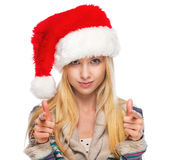 Portrait of happy teenage girl in santa hat pointing in camera Stock Image