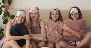 Teenage girls with pillows on bed during pajama party. Portrait of happy teenage girls in nightdress holding pillows during pajama party stock video footage