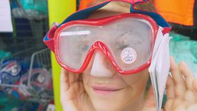 Portrait of a happy teenage who measures the mask for scuba diving in the store. stock images