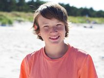 Portrait of a happy teenager boy on the beach stock photo