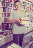 Portrait of happy teenager boy with book pile. In shop Royalty Free Stock Image