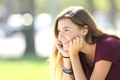 Happy teenager looking forward in a park. Portrait of a happy teenager looking forward sitting in a park Royalty Free Stock Images