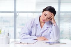 Portrait of a happy thoughtful female doctor stock images