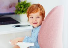 Portrait of happy toddler baby boy is sitting in chair at working place royalty free stock image
