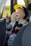 Portrait happy toddler boy sitting in the car Stock Photography
