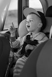 Portrait happy toddler boy sitting in the car Stock Image