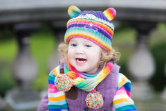 Portrait of a happy toddler girl in colorful knitted hat Stock Photography