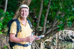 Portrait of a happy tourist with a backpack. Against the backdrop of the jungle in Thailand Royalty Free Stock Photography