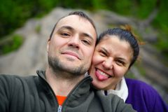 Portrait of happy tourist couple taking selfie in forest Royalty Free Stock Image
