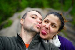 Portrait of happy tourist couple taking selfie in forest Stock Photo