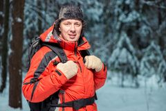 Portrait of a happy tourist in a jacket hiking with a backpack i. N the winter forest Royalty Free Stock Photos