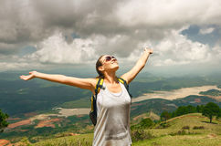 Portrait of happy traveler girl with raised up hands enjoying va Stock Photos
