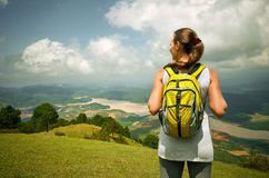 Portrait of happy traveler woman with backpack standing on top o. F the mountain and enjoying valley view Stock Photography