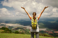 Portrait of happy traveler woman with backpack standing on top o. F the mountain and enjoying valley view with raised hands Stock Photography