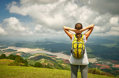 Portrait of happy traveler woman with backpack standing on top o. F the mountain and enjoying valley view with raised hands Royalty Free Stock Image