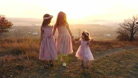 Portrait of happy tree girls in the meadow. Portrait of happy mother with tree her doughters sits in the meadow. Amazing sunset in autumn day. Girls dressed in stock video