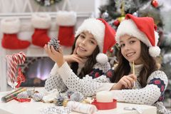 Girls preparing for Christmas. Portrait of happy twin girls in Santa hats preparing for Christmas sitting at the table Stock Photography