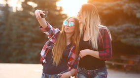 Portrait of a happy two smiling girls making selfie photo on smartphone. urban background. The evening sunset over the. Portrait of a happy two smiling girls stock video