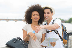 Portrait happy vacationing couple standing against garonne river Royalty Free Stock Image