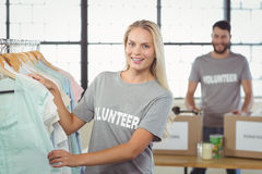 Portrait of happy volunteer choosing clothes for donation Stock Image