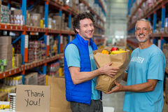 Portrait of happy volunteers holding a grocery bag stock photo