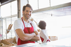 Portrait of a happy waiter with arms crossed. At the bakery Royalty Free Stock Photography