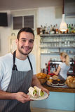 Portrait of happy waiter with fresh rolls at cafe Royalty Free Stock Photography