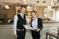 Portrait of happy waiter and waitress in restaurant Royalty Free Stock Photo