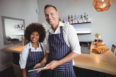 Portrait of happy waiter and waitress using digital tablet at counter Stock Photos