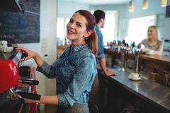 Portrait of happy waitress with co-worker talking to customer at coffee shop Royalty Free Stock Photos