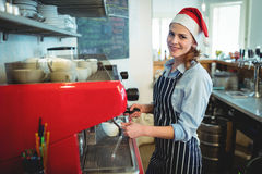 Portrait of happy waitress wearing Santa hat at cafe Stock Photography