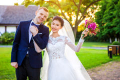 Portrait of happy wedding couple holding hands while standing at lawn Stock Photography