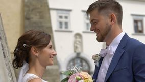 Portrait of happy weding pair. Adorable groom with wedding bouquet of colourful roses coming to his attractive bride stock video