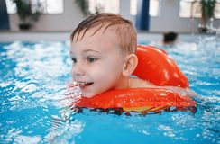 White Caucasian child in swimming pool. Preschool boy  training to float with red circle ring in water. Portrait of happy white Caucasian child in swimming pool Royalty Free Stock Image