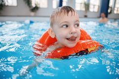 White Caucasian child in swimming pool. Preschool boy  training to float with red circle ring in water. Portrait of happy white Caucasian child in swimming pool Stock Images