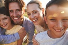 Portrait of happy white family embracing outdoors, close up stock photo
