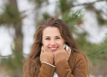 Portrait of happy woman against fir-tree in winter outdoors Stock Photo