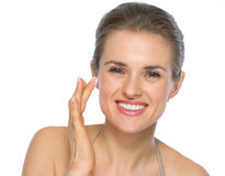 Portrait of happy woman applying creme on face Royalty Free Stock Image