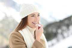 Woman applying lip balm in snowy winter. Portrait of a happy woman applying lip balm in winter with a snowy mountain in the background stock image