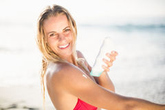 Portrait of happy woman applying sunscreen lotion on the beach Stock Photography