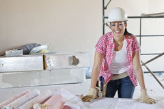 Portrait of a happy woman architect with building plans stock photo