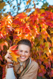 Portrait of happy woman with autumn leafs in front of foliage Royalty Free Stock Image