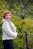 Portrait of the happy woman of average years against the background of autumn trees Stock Photo