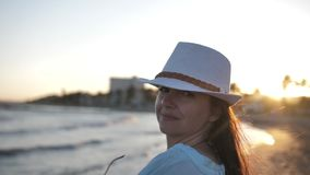 Portrait of a happy woman on the beach at sunset flirts and looks at the camera, travel concept. 1080p stock video footage
